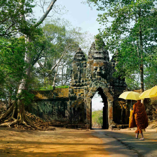 Monks with umbrella walking in Angkor Wat, Cambodia